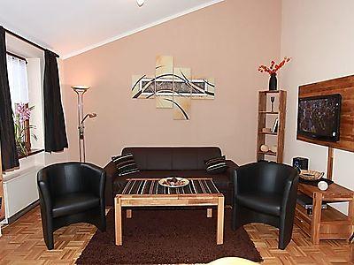 neu gestalteter Wohnraum mit Echtholz-Eichenmöbeln, einem Leder-Schlafsofa für 2 Pers. und Flachbildschirm